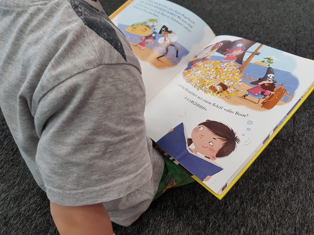 kind hat Buch auf dem Schoß