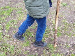 Kinderbeine mit Wanderstock auf der Wiese